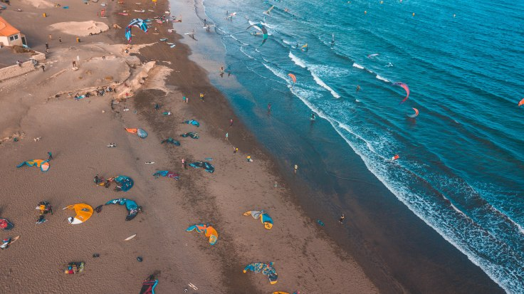 Viele Kites und Segel liegen am Strand verteilt.