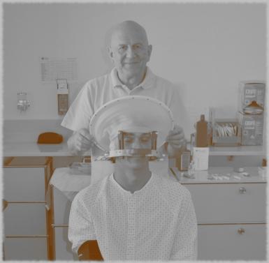 Der Patient im Rollstuhl sitzend mit einer metallischen Krone, die am Kopf befestigt wurde. Im Hintergrund einer der behandelnden Ärzte.