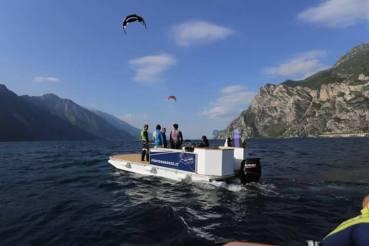 Das Platform Boot des Vereins auf dem See. Die Sonne scheint und im Hintergrund sieht man 2 Kites.