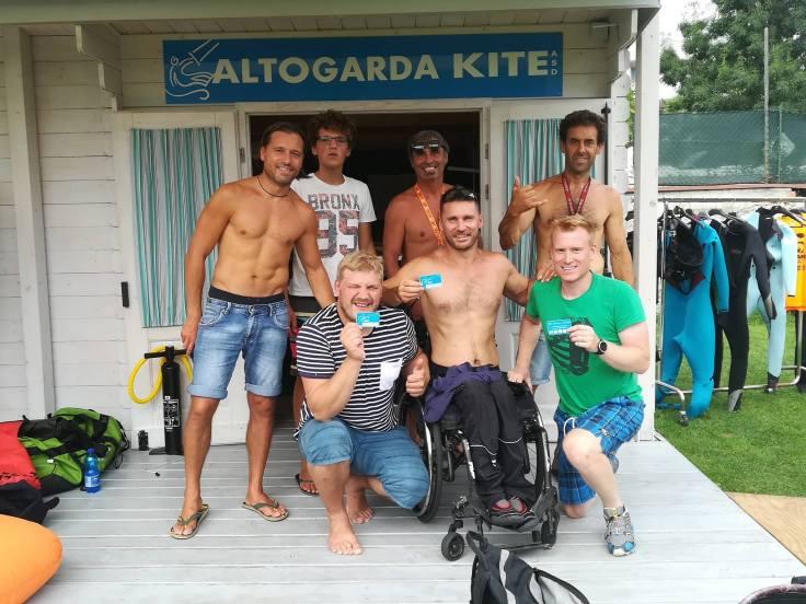 Ein Rollstuhlfahrer und zwei weitere Kiteschüler zeigen die frisch erworbene Mitgliedskarte. Auch Gründungsmitglieder des Vereins lächeln in die Kamera. Im Hintergrund das Gartenhäuschen des Vereins mit dem Schriftzug 'Altogarda Kite'.