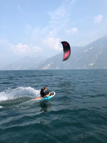 Ein Sitkiteboarder auf dem Wasser. Hinter dem Board sieht man den Spray des Wassers. Im Hintergrund ist der Kite zu sehen.