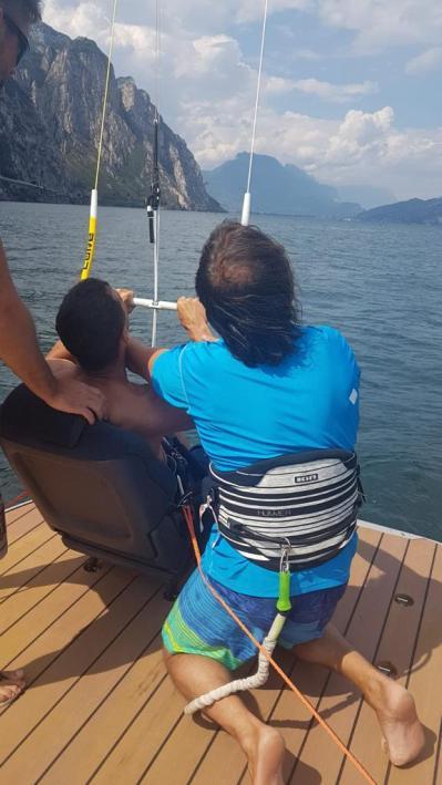 Ein Kiteschüler sitzt sicher in einem Autositz auf dem Boot und lernt die Kite-Steuerung. Der Kitelehrer kniet daneben und unterstützt den Schützling.