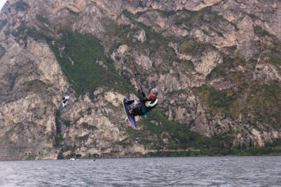 Sitzender Kitesurfer bei einem Sprung am Gardasee.