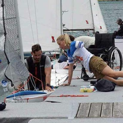 Vorbereitung des Boots. Eine junge Frau mit amputiertem rechtem Arm kniet am Steg. Ein dunkelhaariger mit sitzt im Boot. Im Hintergrund sieht man einen leeren Rollstuhl.