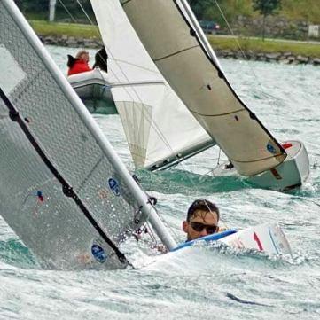 2 2.4mR Boote während eines Rennens. Beim vorderen Boot sieht man nur den Kopf des Lenkers. Aufgrund der Krängung streifen die Segel das Wasser.