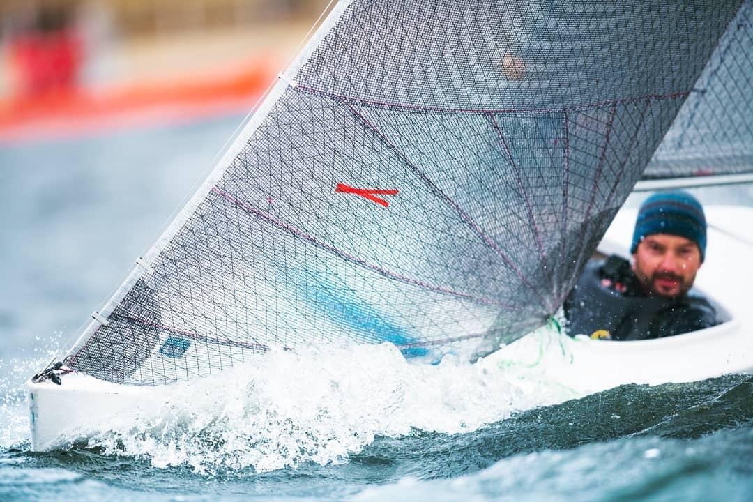 Nahaufnahme Segelboot in voller Fahrt. Das Segel ist vom Wind gebläht. Recht im Hintergrund sieht man den Segler etwas unscharf mit blauer Mütze.