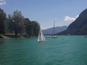 See bei Sonnenschein. Im Zentrum ein 2.4mR Boot. Im Hintergrund sieht man ein paar geankerte Boote sowie das Ufer mit Bäumen und Gebirge in der Ferne.