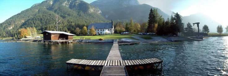 Weitwinkelaufnahme vom See aus auf die Anlage des TWV. In der Mitte des Bildes der Steg umgeben von Wasser. Im Hintergrund sieht man ein Bootshaus, eine Liegewiese, das Prälatenhaus und ganz hinten bewaldetes Gebirge.