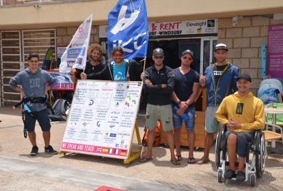 A group of people with 2 IKO flags. One of the group is a wheelchair user.