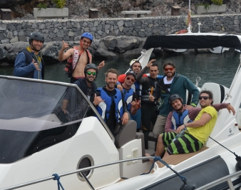 The whole crew in a boat. Some make the hang loose sign with their hands.
