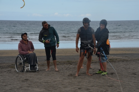 from left to right: wheelchair user with headset, head instructor and the kiteboarding student with helmet and harness and the kite conneted to it. With the student is another instructor - also with helmet.