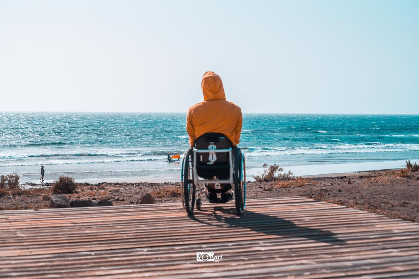 Wheelchair user with a yellow hoody on a wooden plattform on the beach. The photo is taken from behind. The hood covering the head. In the background is the sea with one windsurfer on the shore.