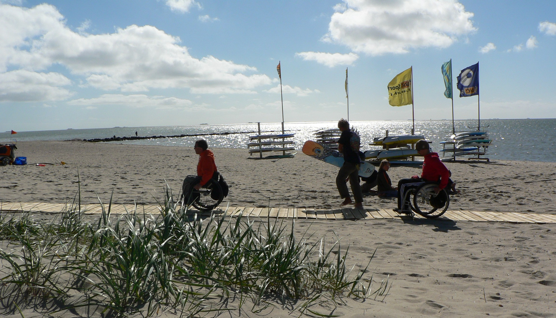 2 wheelchair-users on a ramp on the beach.