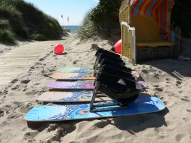 Four empty sitkite-boards on the sand next to the ramp that leads to the beach.