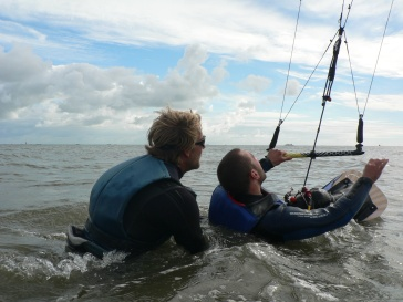 Adaptive kiteboarder on the boar din the sea with a kite. The instructor is behind him to help with the balance.