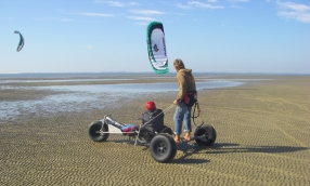 A person with red helmet sits in an adapted kitebuggy. Behind him on the axle of the buggy stands a man to help with the steering.
