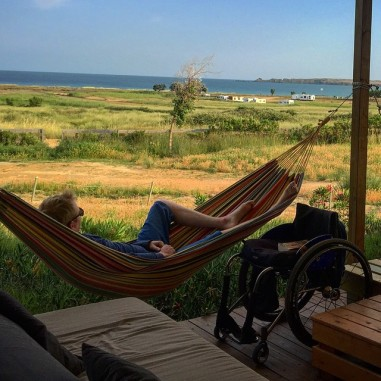Man lying in a hammock. Next to him a wheelchair. In the background the steppe and the bay.