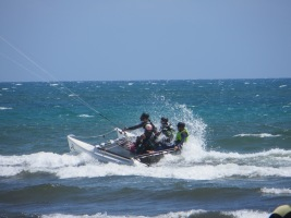 A hobie cat with a kite instead of a sail. 4 people sitting on top. White spray from the speed.