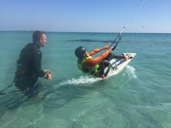 A sitting kiteboarder during the start. Behind him the kite instructor has just let go of the board.