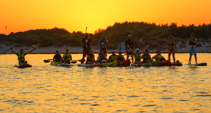 A group of people in kayaks or standing on SUPs. The sun is going down.