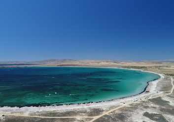 A drone-foto of the bay. In the turqoise water you can see the white lines produced by kiters and windsurfers.