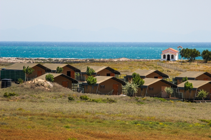The green and yellowish steppe in front. In the middle you see the greenish tents. In the background a small white chappell next to olive trees. Behind it the blue sea with some white caps.