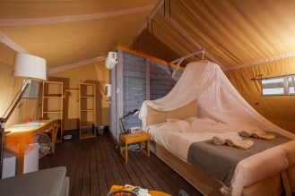 Tent from inside: A double bed and in the background the wooden wall of the bathroom.