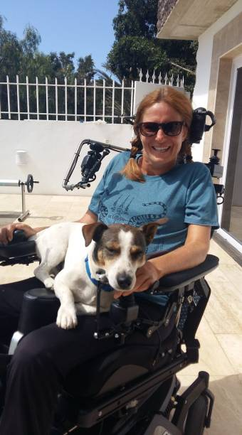 Woman in an electric wheelchair wearing sunglasses. A small dog sits on her lap.