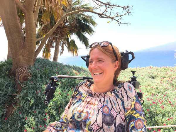 Woman in an electric wheelchair. In the background you green nature and the sea