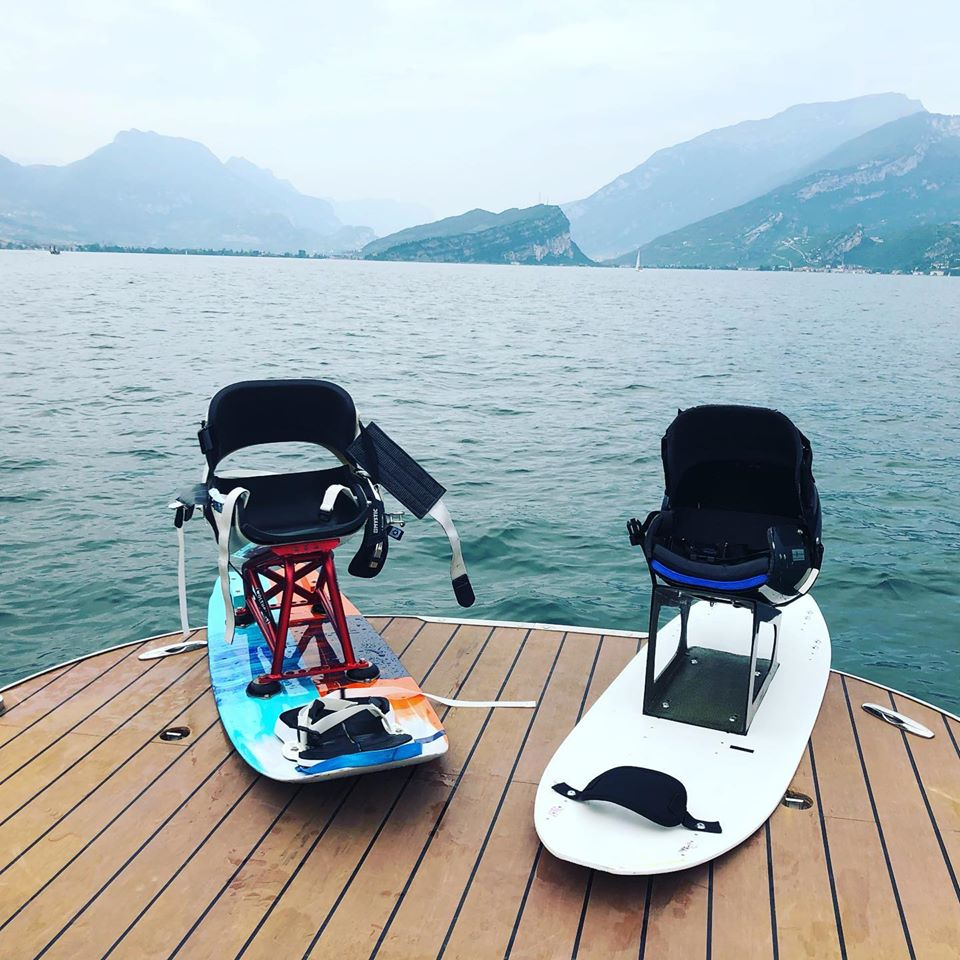 2 different sitkite boards on a boat in a lake.