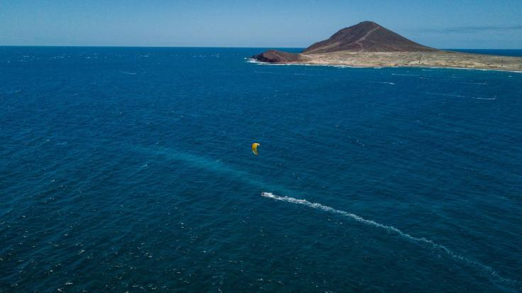 A single yellow kite within a big bay. A small mountain in the background.